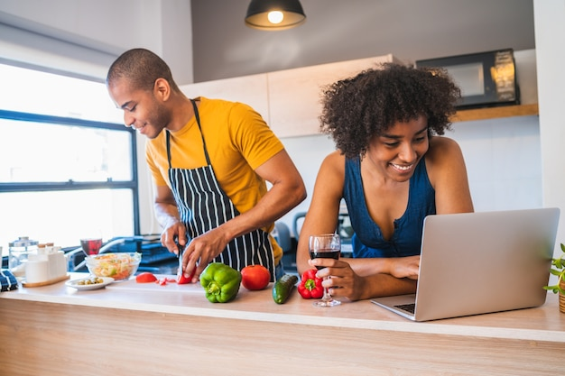 Portret van jonge latijns-paar met behulp van een laptop tijdens het koken in de keuken thuis