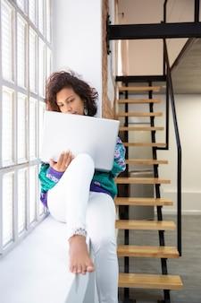 Portret van jonge latijns-vrouw die met haar laptop thuis werkt. ruimte voor tekst.