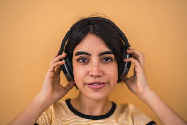 Portret van jonge latijns-vrouw, luisteren naar muziek met een koptelefoon