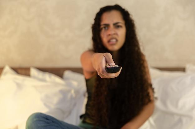 Portret van jonge latijns-vrouw met afstandsbediening in bed liggen en tv kijken.