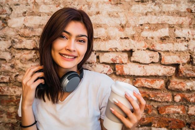 Portret van jonge latijns-vrouw met hoofdtelefoons tegen bakstenen muur