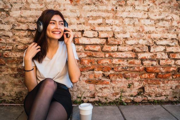 Portret van jonge latijns-vrouw ontspannen en luisteren naar muziek met koptelefoon op bakstenen muur. stedelijk concept.