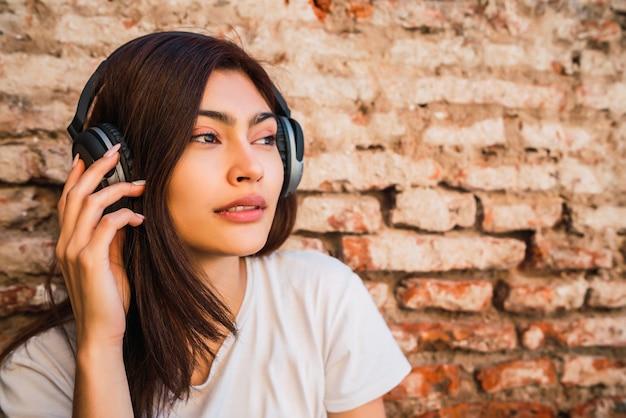 Portret van jonge latijns-vrouw ontspannen en luisteren naar muziek met koptelefoon tegen bakstenen muur. stedelijk concept.