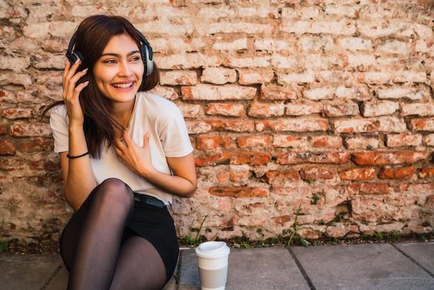 Portret van jonge latijns-vrouw ontspannen en luisteren naar muziek met koptelefoon tegen bakstenen muur.