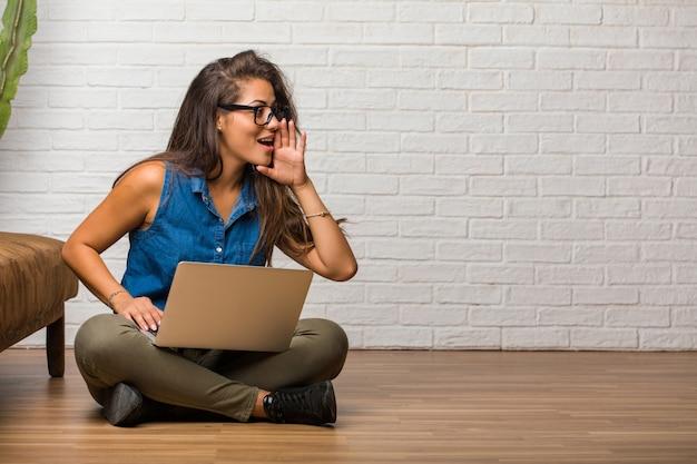 Portret van jonge latijns-vrouw zittend op de vloer fluisteren roddel ondertoon