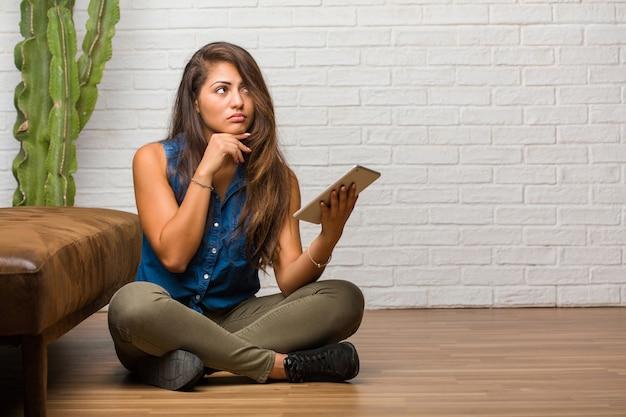 Portret van jonge latijns-vrouwenzitting op de vloer die en omhoog denken denken, verward over een idee