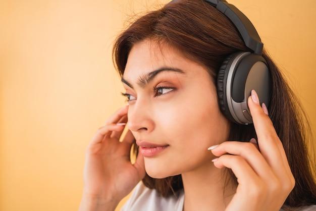 Portret van jonge latijnse vrouw die aan muziek met hoofdtelefoons tegen gele muur luistert. stedelijk concept.