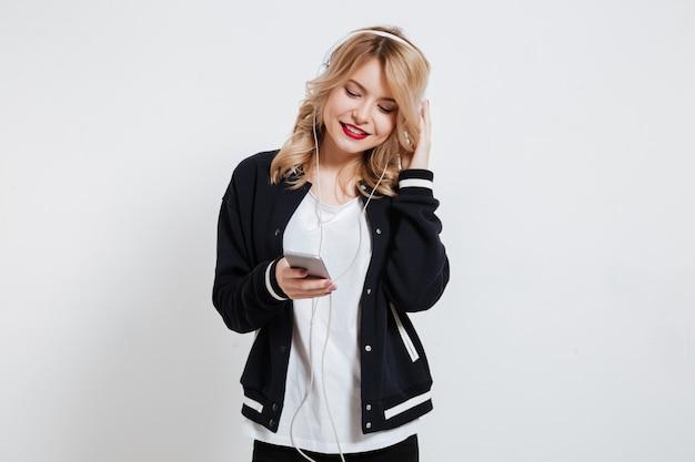 Portret van jonge leuke jonge vrouw die aan muziek met oortelefoons luistert