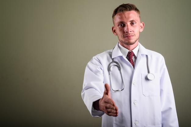 Portret van jonge man arts tegen gekleurde muur