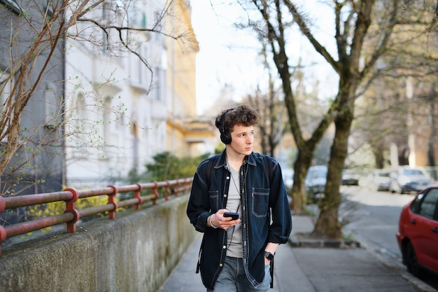 Portret van jonge man forens met koptelefoon wandelen buiten in de stad, met behulp van smartphone.