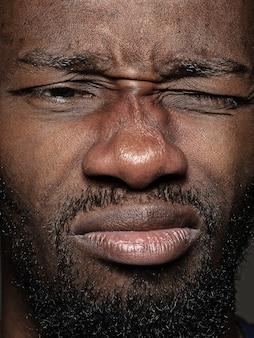 Portret van jonge man knipogen close-up