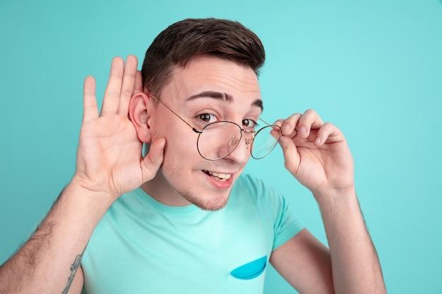 Portret van jonge man luistert naar geheimen geïsoleerd op aquamarijn studio muur aqua