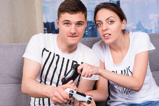 Portret van jonge mannelijke en vrouwelijke gamers die videogames spelen die samen thuis op een bank zitten in een ontspannen sfeer