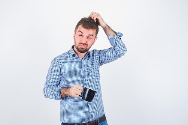 Portret van jonge mannelijke hoofd krabben terwijl cup in shirt, spijkerbroek en peinzende vooraanzicht kijken