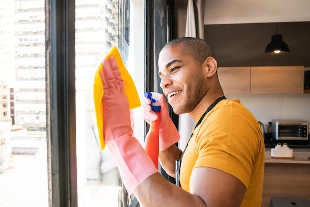 Portret van jonge mannelijke huishoudster die glasvenster thuis schoonmaken