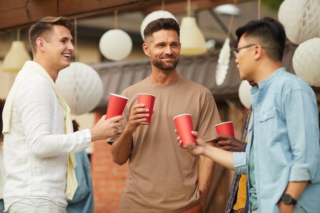 Portret van jonge mannen bier drinken en hoeden tijdens buitenfeest in de zomer
