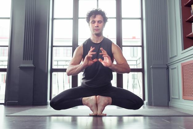 Portret van jonge mannen die aan het trainen zijn met vlinderyoga-pose
