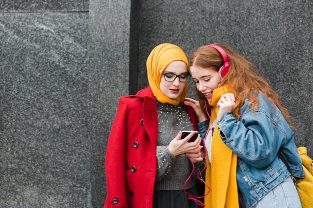 Portret van jonge meisjes die aan muziek luisteren