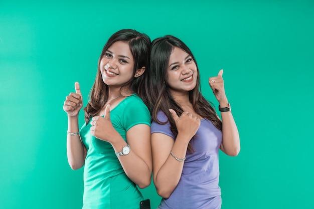 Portret van jonge meisjes tweeling leuk charmant vrolijk terwijl duimen naar de camera geïsoleerd op groene achtergrond wordt weergegeven