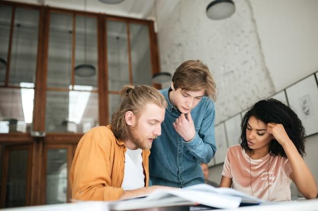 Portret van jonge mensen die bedachtzaam iets in bureau bespreken