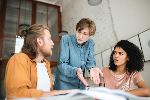 Portret van jonge mensen die emotioneel iets in bureau bespreken