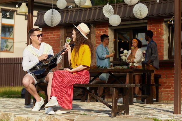 Portret van jonge mensen genieten van buiten partij in de zomer met de nadruk op man gitaarspelen aan vriendin op voorgrond