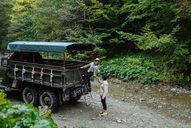 Portret van jonge mensen op een achtergrond van aard. man helpt het meisje om uit de vrachtwagen te komen terwijl ze langs de beek loopt