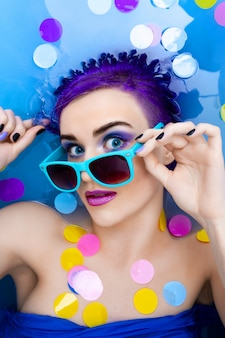 Portret van jonge mode vrouw met paars haar en make-up ontspannen in bad.