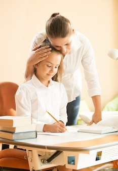 Portret van jonge moeder die dochter prees die huiswerk doet aan bureau