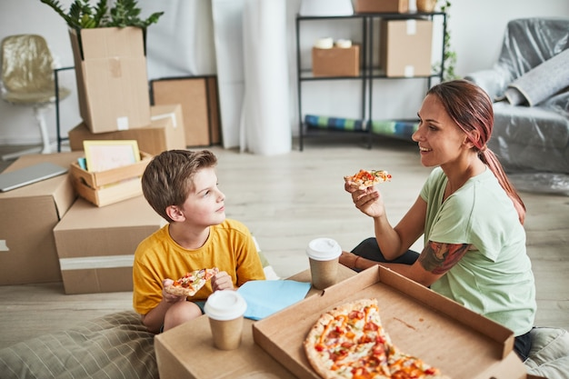Portret van jonge moeder en zoon die pizza uit een kartonnen doos eten terwijl ze vieren dat ze verhuizen naar een nieuwe...