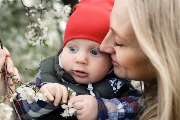 Portret van jonge moeder met blonde baby buitenshuis. gelukkig gezin. mama met baby. Premium Foto
