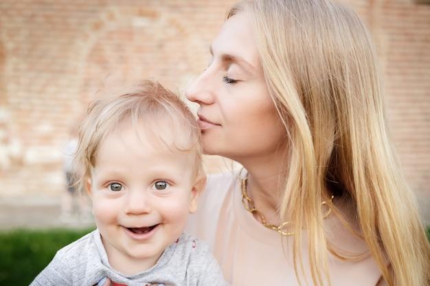 Portret van jonge moeder met blonde baby buitenshuis. gelukkig gezin. mama met baby.