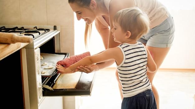 Portret van jonge moeder met peuterzoon die koekjes in oven bakt