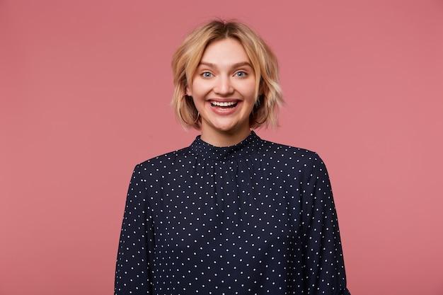 Portret van jonge mooie aantrekkelijke blonde vrouw gekleed in blouse met polka dots, heeft gezichtsuitdrukking verlaten, positief, glimlachen, gelukkig, geïsoleerd tonen