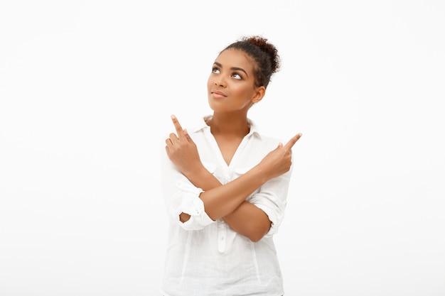Portret van jonge mooie afrikaanse meisje op een witte muur