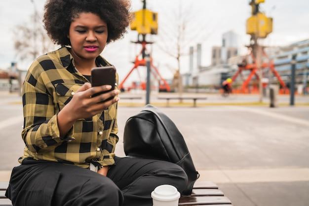 Portret van jonge mooie afro amerikaanse latijns-vrouw met behulp van haar mobiele telefoon zittend op een bankje buiten. communicatie concept.