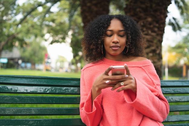 Portret van jonge mooie afro amerikaanse vrouw met behulp van haar mobiele telefoon en zittend op een bankje in een park. buitenshuis.