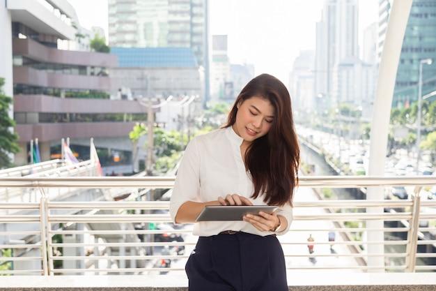 Portret van jonge mooie aziatische onderneemster die in het witte overhemd typen op taplet dragen