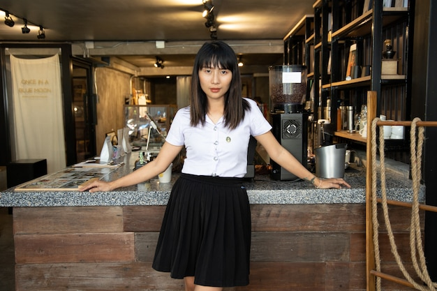 Portret van jonge mooie aziatische school meisje in coffeeshop