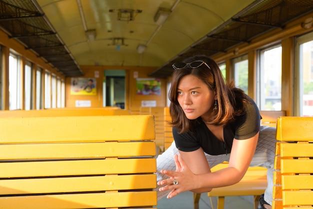 Portret van jonge mooie aziatische toeristenvrouw die de trein berijden bij het station van hua lamphong