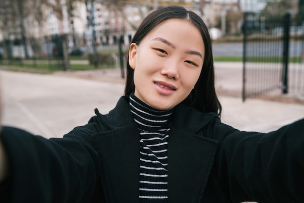 Portret van jonge mooie aziatische vrouw die een selfie buiten in de straat neemt.