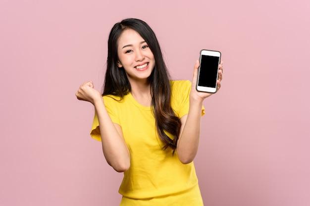 Portret van jonge mooie aziatische vrouw die gelukkig of verrassing voelt en slimme telefoon op roze houdt.