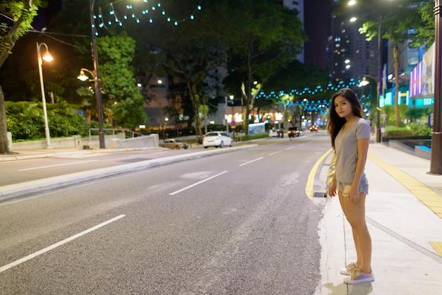 Portret van jonge mooie aziatische vrouw die in de stadsstraten bij nacht in kuala lumpur, maleisië dwaalt