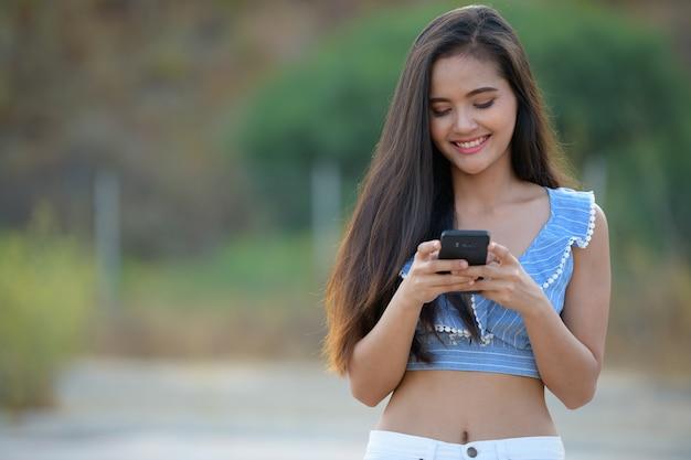 Portret van jonge mooie aziatische vrouw die mobiele telefoon buiten met behulp van