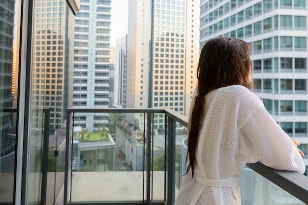 Portret van jonge mooie aziatische vrouw die vanaf het balkon van het uitzicht over de stad geniet