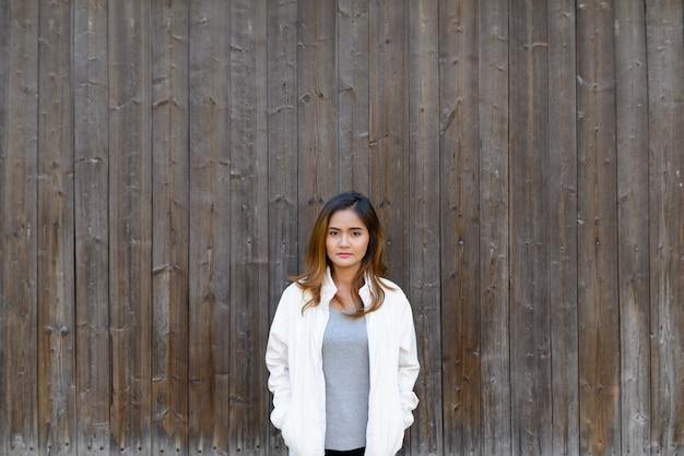 Portret van jonge mooie aziatische vrouw die zich tegen houten muur bevindt