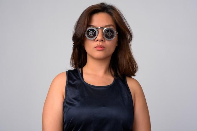 Portret van jonge mooie aziatische vrouw die zonnebril met doelontwerp draagt