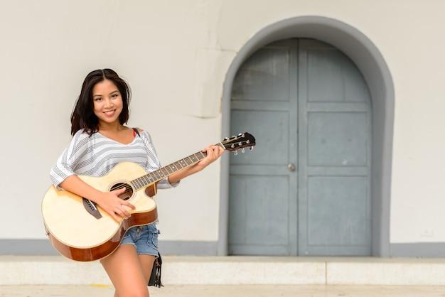 Portret van jonge mooie aziatische vrouw gitaarspelen in de straten van de stad buitenshuis