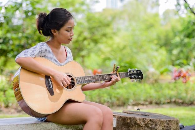 Portret van jonge mooie aziatische vrouw gitaarspelen in het park buiten