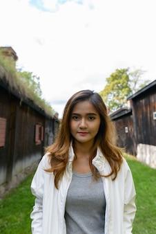 Portret van jonge mooie aziatische vrouw in het midden van uitgelijnde oude houten plattelandshuisjes